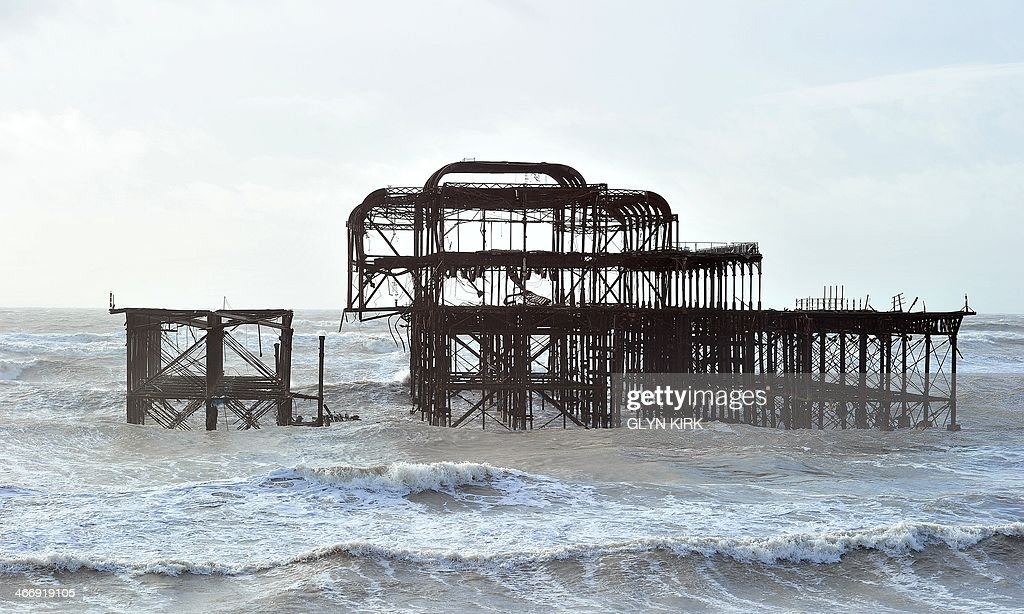 Brighton's West Pier in southern England is divided into two parts after rough seas caused a section on the east side to collapse February 5, 2014. More than 8,000 homes were without power in southwest England on Wednesday after fresh storms battered the region, sending huge waves crashing onto the coastline and damaging sea defences.