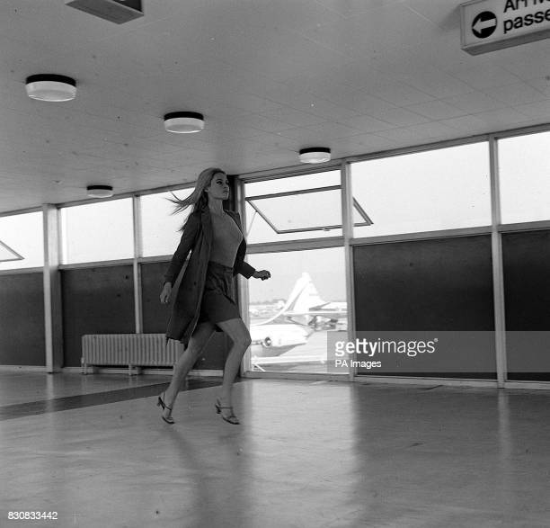 Brigitte Bardot a film traveller in a hurry races along a corridor at Heathrow Airport She was filming scenes for her new picture 'Two Weeks in...
