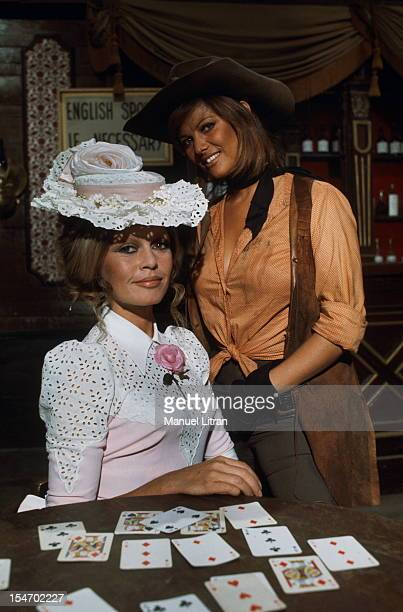 Brigitte Bardot and Claudia Cardinale suit posing together in front of the Wild West of playing cards while shooting the film 'The Petroleuses'...