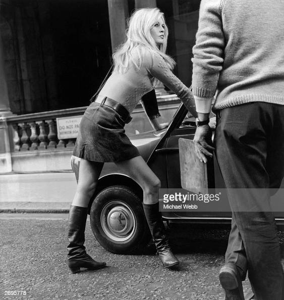 Brigitte Bardot during a break from filming 'Two Weeks in September' in Whitehall London Leaning against a mini she is wearing boots a belted...