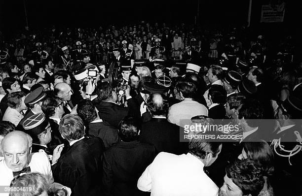 Brigitte Bardot et Gunter Sachs entourés de policiers tentent de se frayer un chemin dans la cohue des journalistes pour entrer dans le palais des...