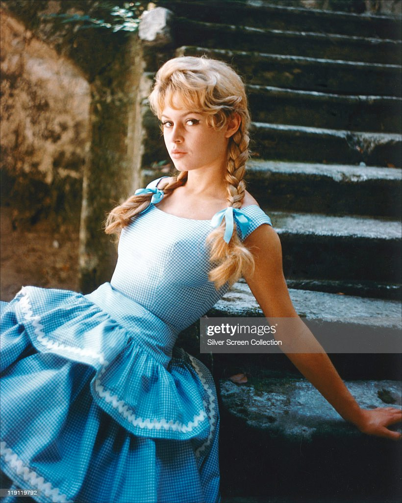 Brigitte Bardot French actress model and singer wearing a blue gingham dress with her hair in plaits tied with blue bows sitting in a series of stone...