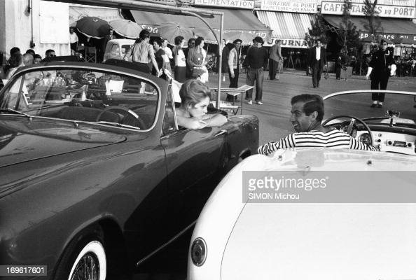 Brigitte Bardot in her cabriolet Simca and Roger Vadim in his spider Lancia Aurealia are photographed for Paris Match on the old port of SaintTropez...