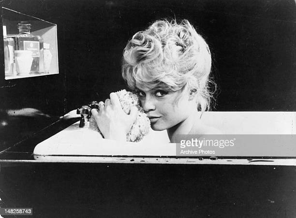 Brigitte Bardot in the bathtub with an seductive look on her face in a scene from the film 'La Parisienne' 1957