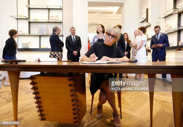 Brigitte Macron wife of French President signs a guestbook during a visit of the First Ladies to a shop of Belgian fashion label Delvaux on May 25 in...