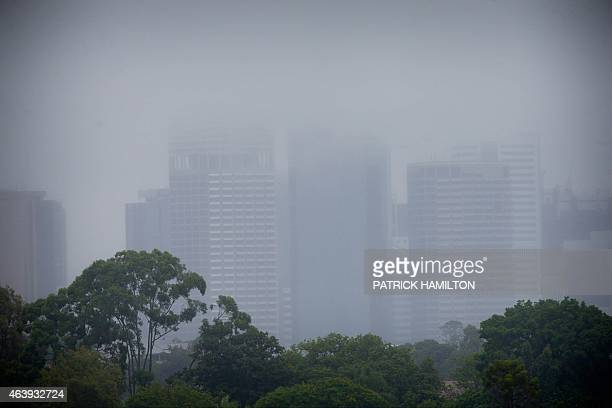 Brisbane CBD buildings are shrouded by low clouds and rain from Tropical Cyclone Marcia in Brisbane on February 20 2015 Two powerful cyclones further...