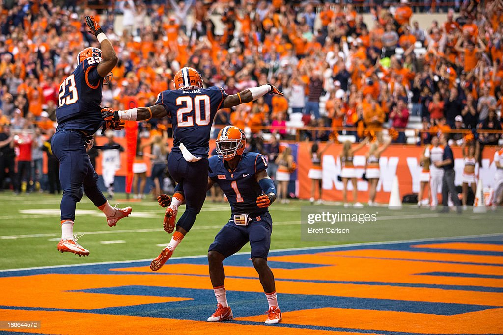 Brisly Estime of Syracuse Orange jumps into the arms of teammate Ashton Broyld after Broyld threw Estime the team's second touchdown pass during a...