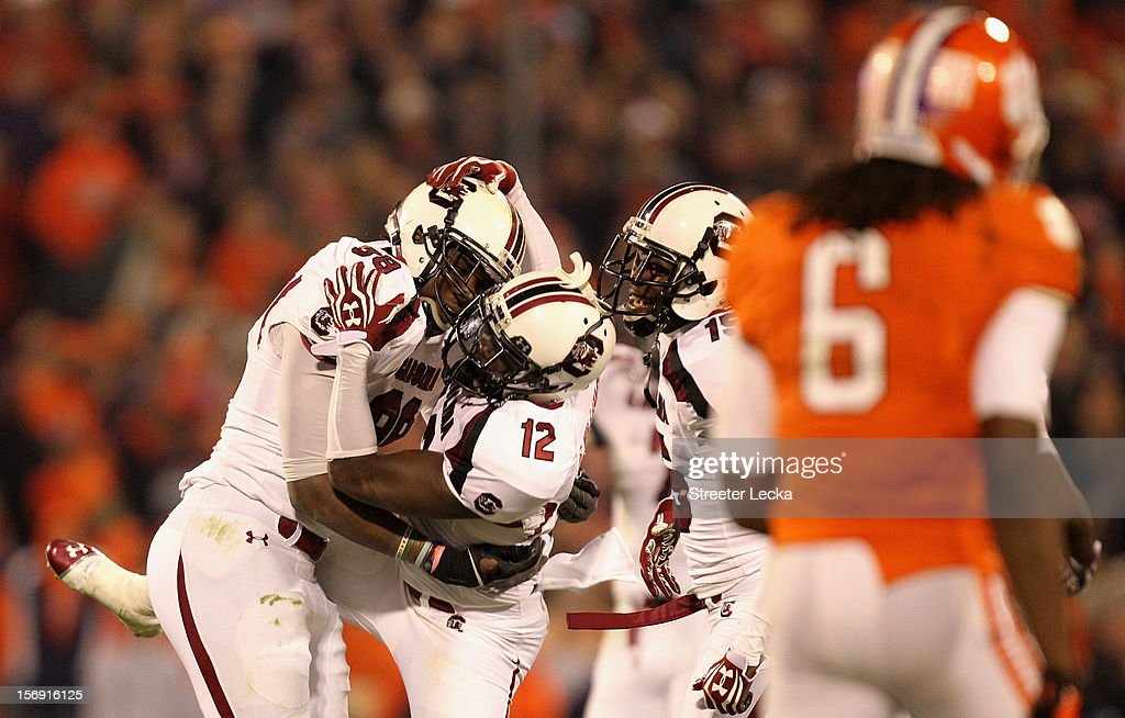 Brison Williams #12 of the South Carolina Gamecocks celebrates after making an interception with teammate Devin Taylor #98 as <a gi-track='captionPersonalityLinkClicked' href=/galleries/search?phrase=DeAndre+Hopkins&family=editorial&specificpeople=7321907 ng-click='$event.stopPropagation()'>DeAndre Hopkins</a> #6 of the Clemson Tigers walks off the field during their game at Memorial Stadium on November 24, 2012 in Clemson, South Carolina.