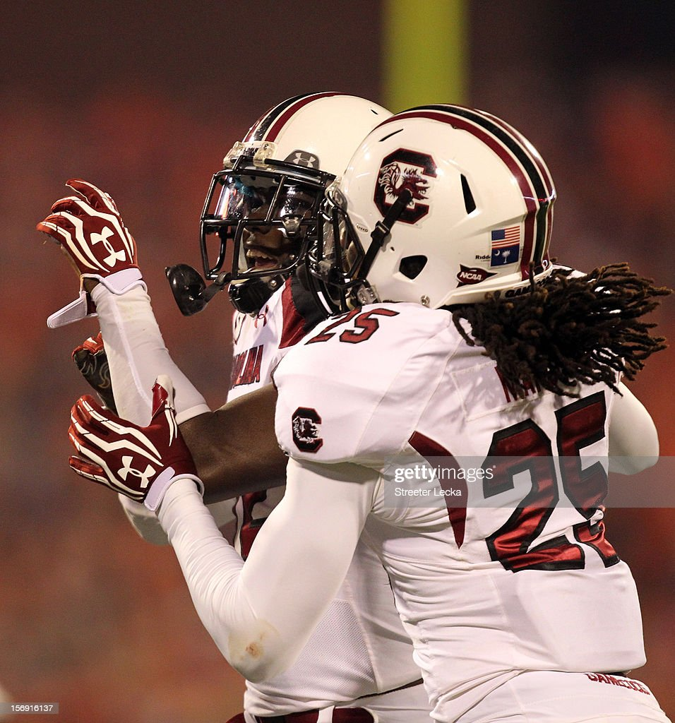 Brison Williams #12 of the South Carolina Gamecocks celebrates after making an interception with teammate Kadetrix Marcus #25 during their game against the Clemson Tigers at Memorial Stadium on November 24, 2012 in Clemson, South Carolina.