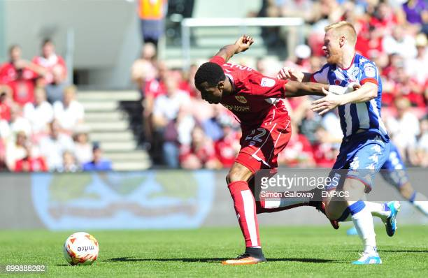 Bristol City's Jonathan Kodjia and Wigan Athletic's David Perkins in action