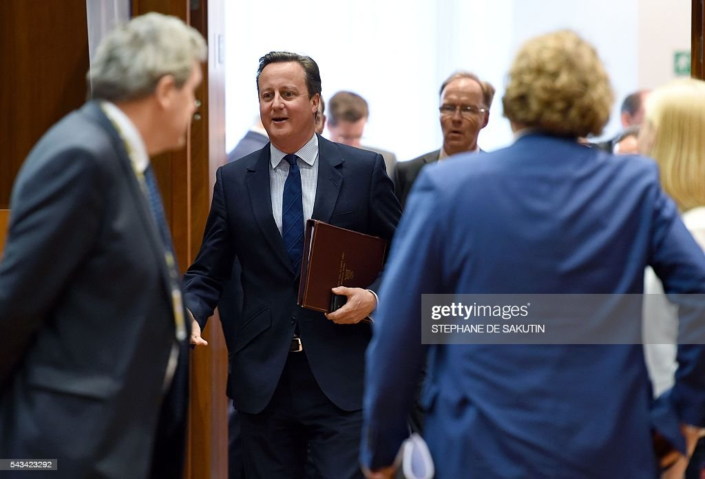 Britain Prime Minister David Cameron (C) reacts as he walks during EU - Summit at the EU headquarters in Brussels on June 28, 2016. Prime Minister David Cameron said today he wants the 'closest possible' relations with the EU after Britain voted to leave the bloc, adding the split should be 'as constructive as possible'. As he arrived at a Brussels summit, Cameron, who is to step down within weeks, told reporters that, while Britain was leaving the EU, 'we mustn't be turning our backs on Europe.' SAKUTIN