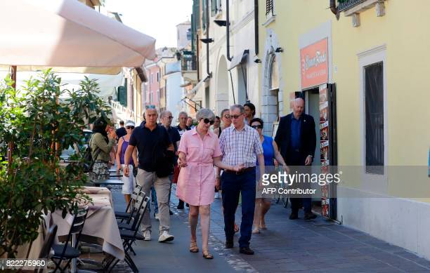 TOPSHOT Britain Prime Minister Theresa May walks with her husband Philip in Desenzano del Garda by the Garda lake as they holiday in northern Italy...