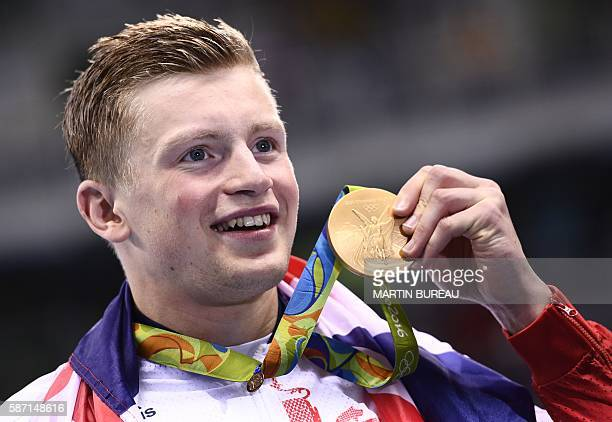 Britain's Adam Peaty poses on the podium with his gold medal after he broke the World Record in the Men's 100m Breaststroke Final during the swimming...