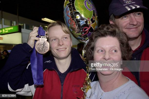 Britain's Alex Coomber clutches her Bronze medal as she amd her husband Eric were met off a flight returning to Britain from the Winter Olympics Mrs...