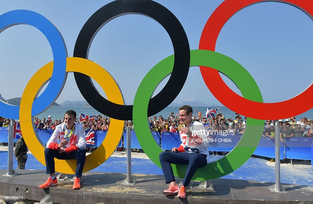 Britain's Alistair Brownlee and Britain's Jonathan Brownlee pose with their medals next to the Olympic rings after the men's triathlon at Fort...