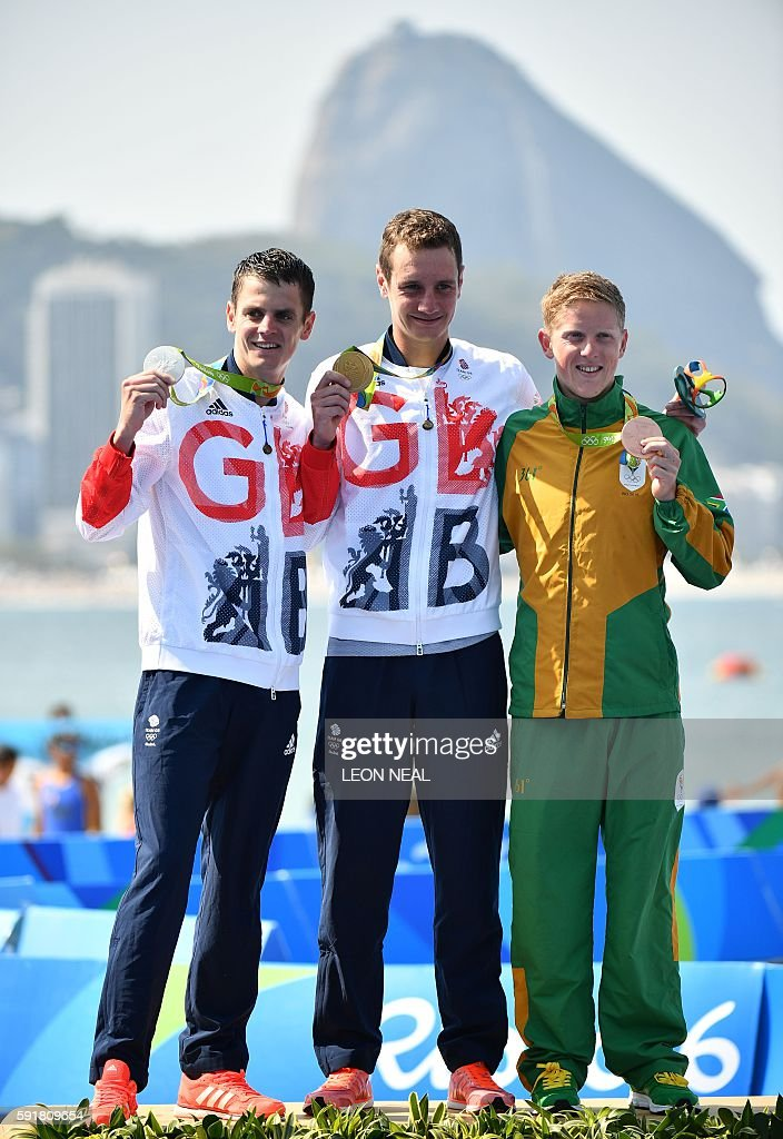 Britain's Alistair Brownlee Britain's Jonathan Brownlee and South Africa's Henri Schoeman pose with their medals after the men's triathlon at Fort...