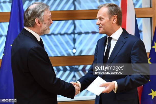 Britain's ambassador to the EU Tim Barrow shakes hands with European Council President Donald Tusk after delivering British Prime Minister Theresa...
