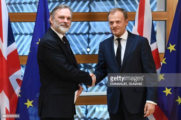 Britain's ambassador to the EU Tim Barrow shakes hands with European Council President Donald Tusk before delivering him British Prime Minister...