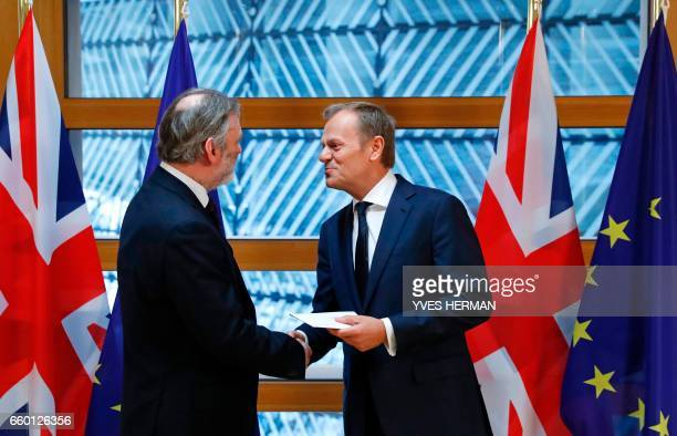 Britain's Ambassador to the EU Tim Barrow shakes hands with European Council President Donald Tusk after handing him the British prime minister's...