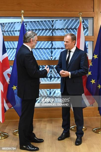 Britain's ambassador to the EU Tim Barrow speaks to European Council President Donald Tusk before handing him British Prime Minister Theresa May's...