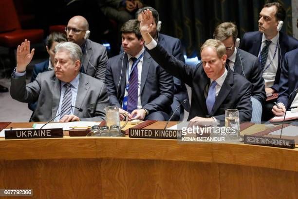 Britain's Ambassador to the United Nations Matthew Rycroft holds up his hand as he votes in favor of a draft resolution that condemns the reported...
