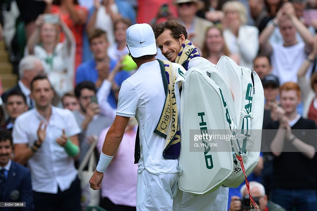 Britain's Andy Murray (R) and Britain's Liam Broady (L) leave the court together after Murray won their men's singles first round match on the second day of the 2016 Wimbledon Championships at The All England Lawn Tennis Club in Wimbledon, southwest London, on June 28, 2016. / AFP / GLYN