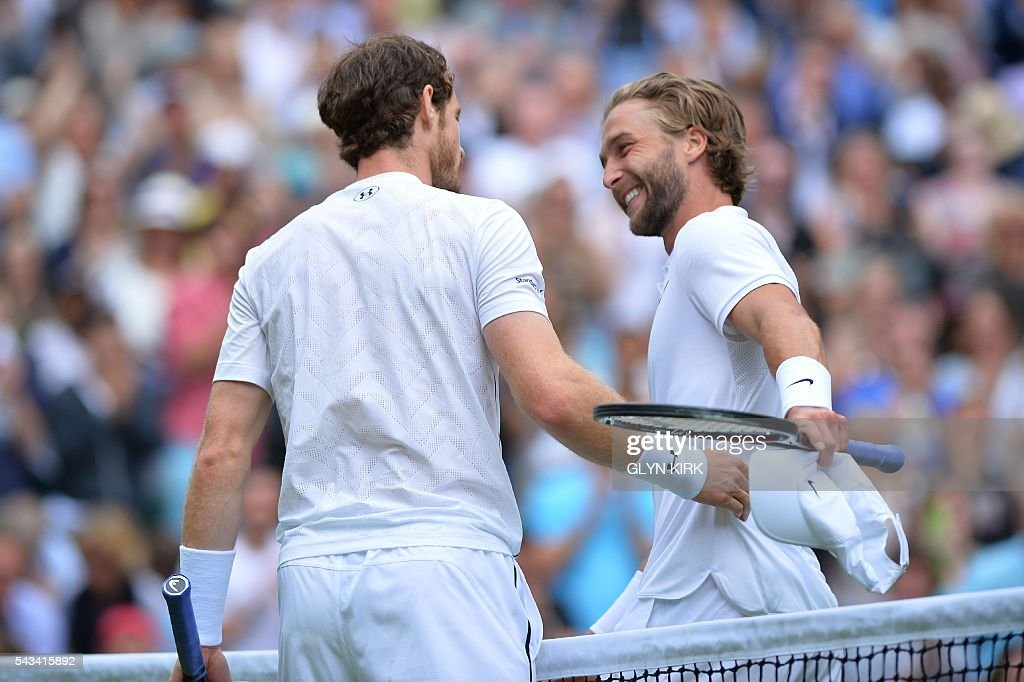 Britain's Andy Murray (L) and Britain's Liam Broady (R) shake hands at the net after Murray won their men's singles first round match on the second day of the 2016 Wimbledon Championships at The All England Lawn Tennis Club in Wimbledon, southwest London, on June 28, 2016. / AFP / GLYN