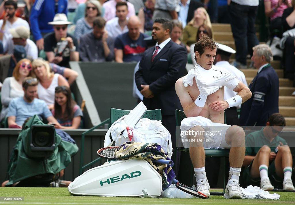 Britain's Andy Murray changes his shirt during a break in play against Taiwan's Lu Yen-hsun during their men's singles second round match on the fourth day of the 2016 Wimbledon Championships at The All England Lawn Tennis Club in Wimbledon, southwest London, on June 30, 2016. / AFP / JUSTIN