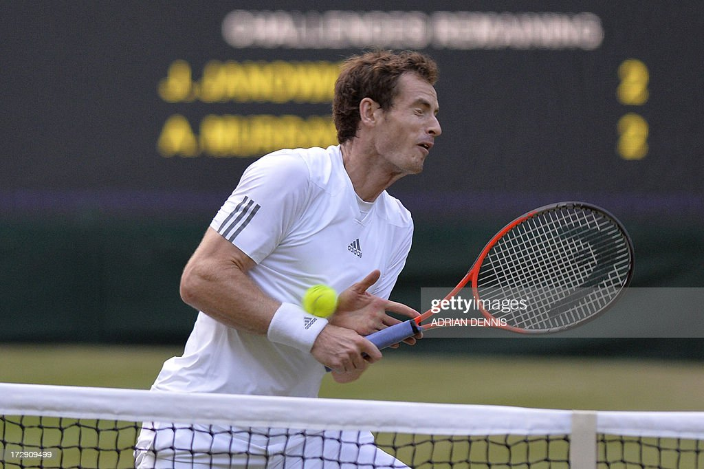 Britain's Andy Murray gets hit by the ball returned by Poland's Jerzy Janowicz in their men's singles semi-final match on day eleven of the 2013 Wimbledon Championships tennis tournament at the All England Club in Wimbledon, southwest London, on July 5, 2013.