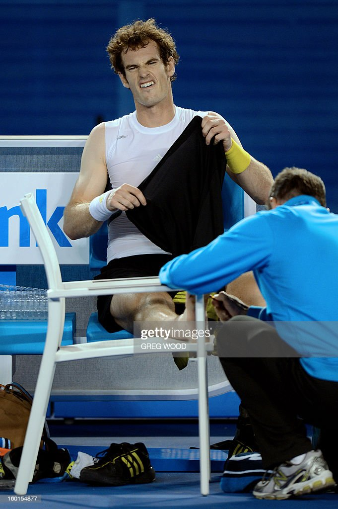 Britain's Andy Murray grimaces as he has his foot tended to during his men's singles final against Serbia's Novak Djokovic on day fourteen of the Australian Open tennis tournament in Melbourne on January 27, 2013.