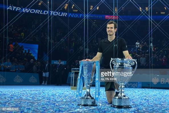 TOPSHOT Britain's Andy Murray poses with both the ATP World Number One trophy and the ATP World Tour Finals trophy after winning the men's singles...