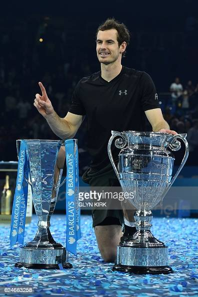 Britain's Andy Murray poses with both the ATP World Number One trophy and the ATP World Tour Finals trophy after winning the men's singles final...