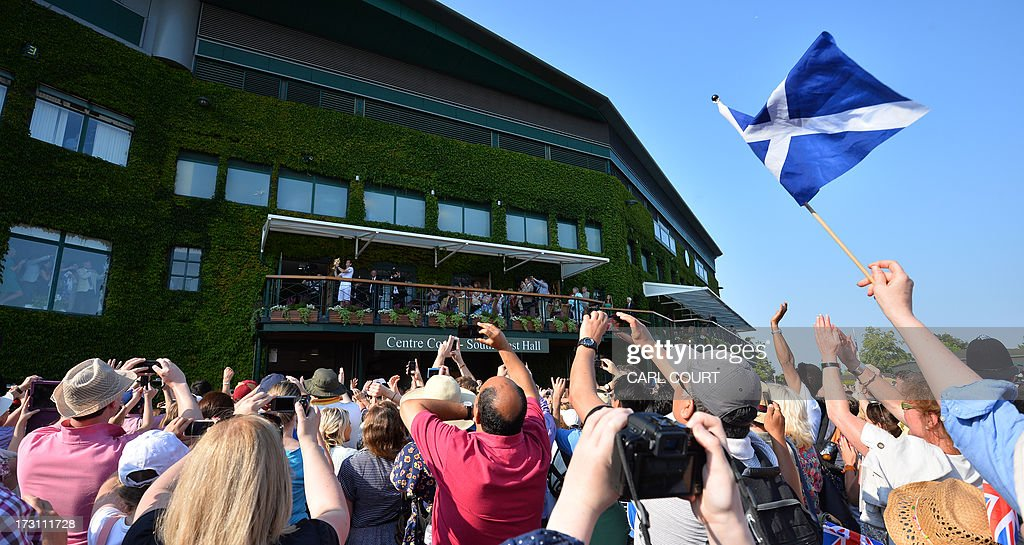 Britain's Andy Murray poses with the winner's trophy on the clubhouse balcony in front of masses of fans one of which waves the Scottish flag (R) after beating Serbia's Novak Djokovic in the men's singles final on day thirteen of the 2013 Wimbledon Championships tennis tournament at the All England Club in Wimbledon, southwest London, on July 7, 2013. Murray won 6-4, 7-5, 6-4.