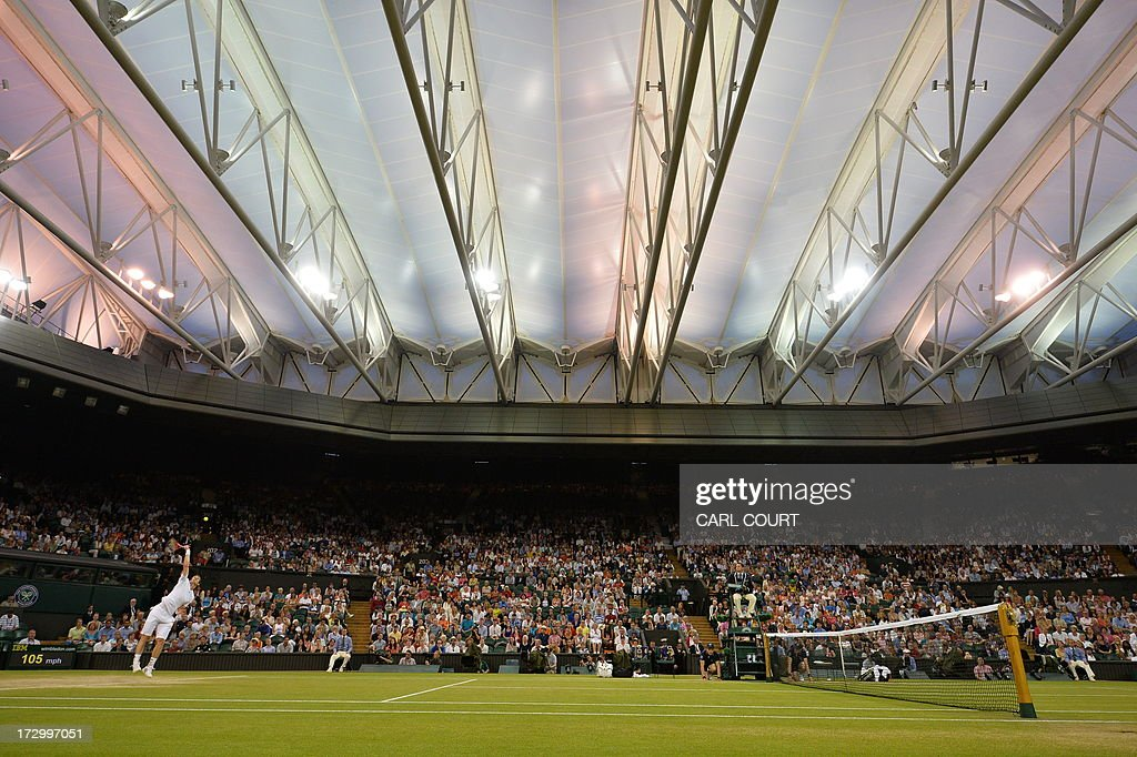 Britain's Andy Murray serves against Poland's Jerzy Janowicz in their men's singles semi-final match on day eleven of the 2013 Wimbledon Championships tennis tournament at the All England Club in Wimbledon, southwest London, on July 5, 2013. AFP PHOTO / CARL COURT - RESTRICTED TO EDITORIAL USE