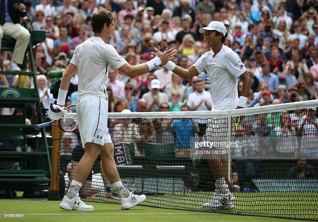 Britain's Andy Murray (L) shakes hands with Taiwan's Lu Yen-hsun after winning their men's singles second round match on the fourth day of the 2016 Wimbledon Championships at The All England Lawn Tennis Club in Wimbledon, southwest London, on June 30, 2016. / AFP / JUSTIN