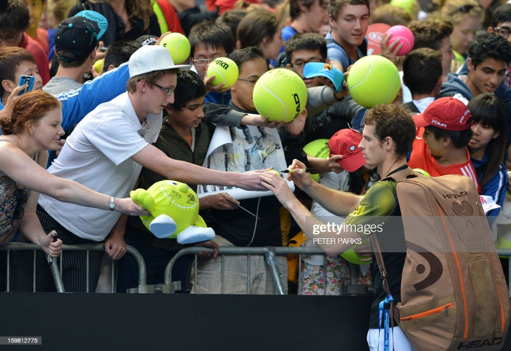 Britain's Andy Murray signs autographs for supporters after victory in his men's singles match against France's Gilles Simon on the eighth day of the Australian Open tennis tournament in Melbourne on January 21, 2013.