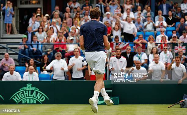 Britain's Andy Murray turns to his teammates as he jumps and celebrates beating France's JoWilfried Tsonga during their Davis Cup world group...