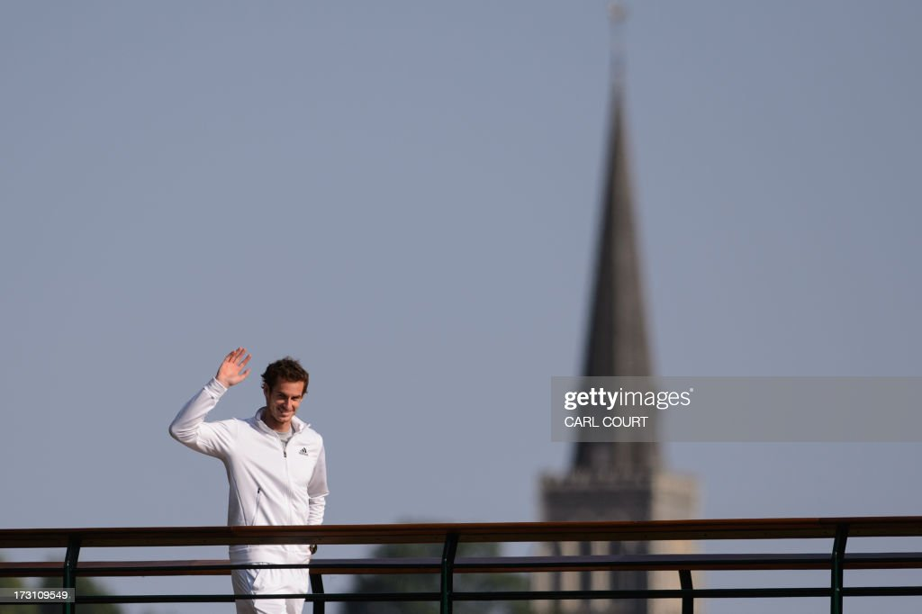 Britain's Andy Murray waves from a walk way after beating Serbia's Novak Djokovic in the men's singles final on day thirteen of the 2013 Wimbledon Championships tennis tournament at the All England Club in Wimbledon, southwest London, on July 7, 2013. Murray won 6-4, 7-5, 6-4.