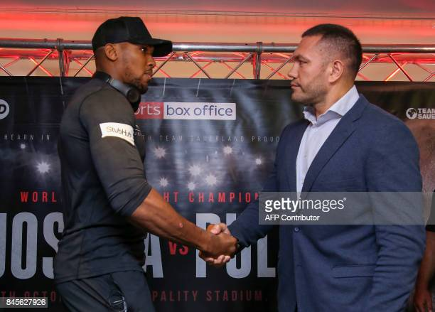 Britain's Anthony Joshua and Bulgaria's Kubrat Pulev shake hands during a press conference at the Principality Stadium in Cardiff on September 11...