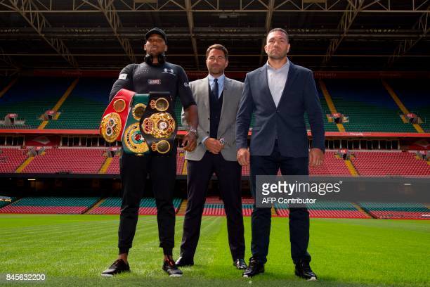 Britain's Anthony Joshua boxing promoter Eddie Hearn and Bulgaria's Kubrat Pulev pose on the pitch at the Principality Stadium in Cardiff on...