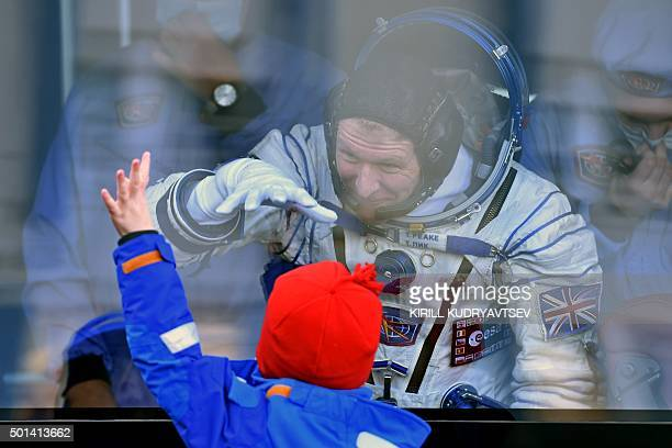 Britain's astronaut Tim Peake gestures to his child from a bus after his space suit was tested at the Russianleased Baikonur cosmodrome prior to...