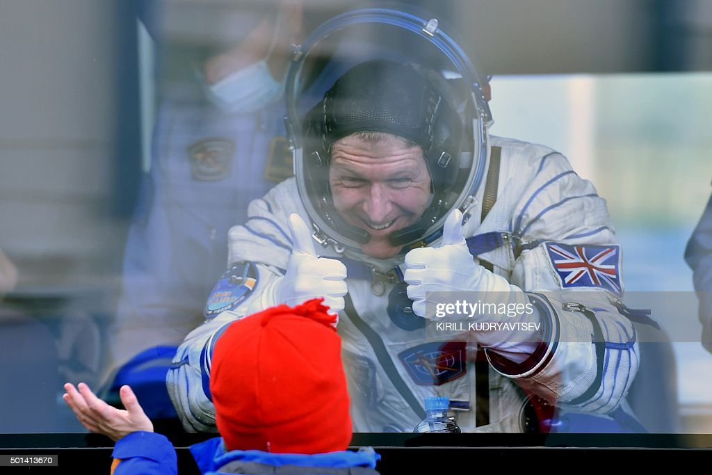 Britain's astronaut Tim Peake gestures to his child from a bus after his space suit was tested at the Russian-leased Baikonur cosmodrome, prior to blasting off to the International Space Station (ISS), on December 15, 2015. Russia's Soyuz TMA-19M spacecraft carrying the International Space Station (ISS) Expedition 46/47 crew of Britain's astronaut Tim Peake, Russian cosmonaut Yuri Malenchenko and US astronaut Tim Kopra is scheduled to blast off to the ISS on December 15, 2015. AFP PHOTO / KIRILL KUDRYAVTSEV / AFP / KIRILL KUDRYAVTSEV