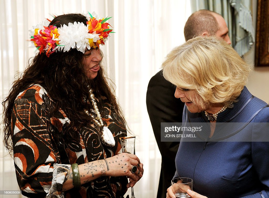 Britain's Camilla, Duchess of Cornwall (R) admires the Maori tattoos on the arm of New Zealand artist Rosanna Raymond, who is wearing a Tuvalu floral headdress made from silk flowers, during a reception for finalists and past winners of 'New Zealander and Australian of the year' at Clarence House in central London on February 6, 2013. The Australia Day Foundation and the New Zealand Society UK, annually present awards to people in the UK who have most advanced the interests of their respective countries in the previous year.