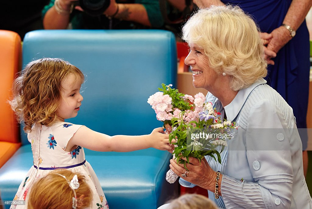 Britain's Camilla Duchess of Cornwall is presented flowers from 2yearold Elisabeth Colquhoun during story time with the Learning English Through...