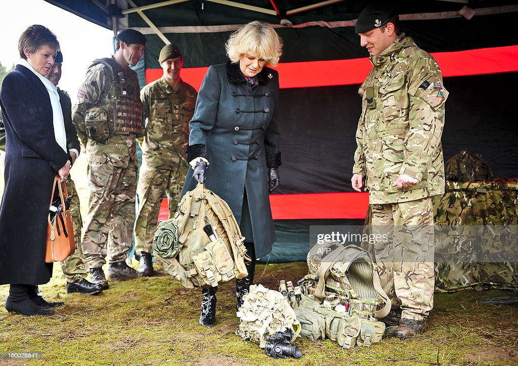 Britain's Camilla, Duchess of Cornwall lifts a soldier's heavy backpack as she is introduced to various pieces of military kit by British soldiers from R Company, 4th Battalion, The Rifles (4 RIFLES), during a visit at Ward Barracks in Bulford, Wiltshire on January 29, 2013. The Duchess of Cornwall, Royal Colonel, 4th Battalion, The Rifles, visited the battalion during their pre-deployment training.