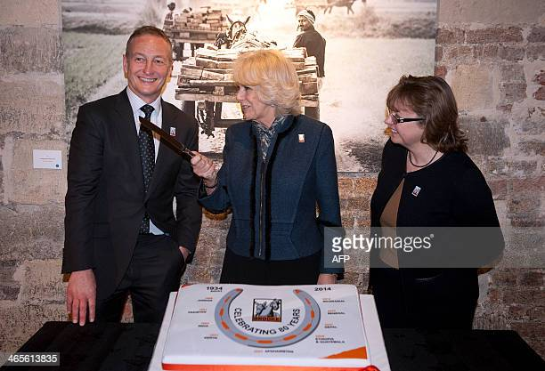 Britain's Camilla Duchess of Cornwall retired jockey and photographer Richard Dunwoody and Chief Executive of Brooke Petra Ingram prepare to cut the...