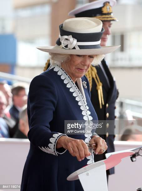 Britain's Camilla Duchess of Cornwall styled as the Duchess of Rothesay while in Scotland presses the button to operate the mechanism to smash a...