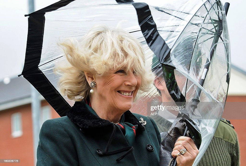 Britain's Camilla, Duchess of Cornwall's umbrella folds up in the wind as she walks with British soldiers from the 4th Battalion, The Rifles during a visit at Ward Barracks in Bulford, Wiltshire on January 29, 2013. The Duchess of Cornwall, Royal Colonel, 4th Battalion, The Rifles, (4 RIFLES), visited the Battalion during their pre-deployment training.