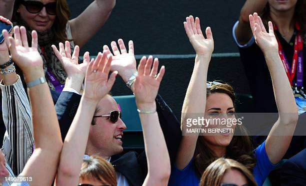 Britain's Catherine and William the Duchess and Duke of Cambridge take part in a Mexican wave while Britain's Andy Murray plays against Spain's...