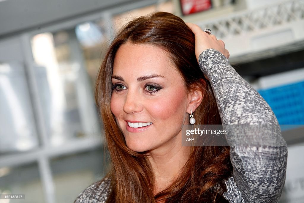 Britain's Catherine, Duchess of Cambridge adjusts her hair during a visit at Hope House charity in south London on February 19, 2013. The Duchess visited Hope House, an all-female rehabilitation centre which is is one of the projects run by her patronage, Action on Addiction.